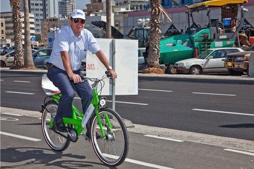 """רון חולדאי רוכב על אופני """"תל אופן"""" בדרך לרמזור"""